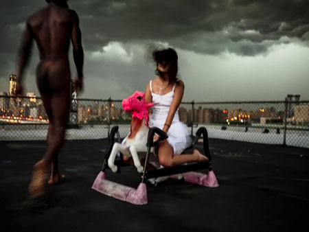 USA. Brooklyn, NY. 2012. A nude man and a girl on a rocking horse spend time on a Williamsburg roof as a storm approaches © Davis Alan Harvey/Magnum Photos