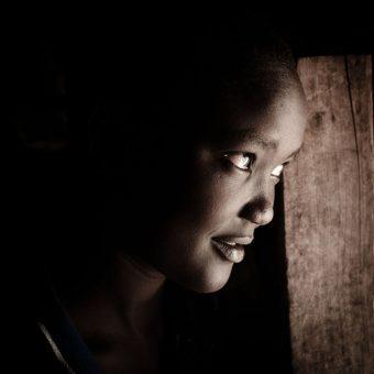 Janet, 14, two years ago escaped from home to avoid FGM and an early forced marriage. Her family wanted to marry her off to a 50 years old man: for the Pokot people, the circumcision rite is necessary before marriage. From Baringo are, she went on a 6 days walk in the bushes until she met Theresa Chepution at the market in Kongelai. Since then, she's been living with Theresa's family. Kongelai. Kongelai, Kenya, 2015.  Janet, 14 anni, due anni fa è scappata di casa per sottrarsi alla MGF e a un matrimonio forzato. La sua famiglia voleva farla sposare con un uomo di 50 anni: per il gruppo etnico dei Pokot, la circoncisione femminile è un necessario rito pre-nuziale. Dall'area di Baringo, Janet si è quindi avventurata in un cammino di 6 giorni nei boschi finché ha incontrato Theresa Chepution al mercato di Kongelai. Da allora, vive con la donna e la sua famiglia. Kongelai, Kenya, 2015.