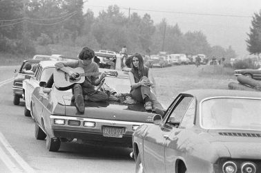 On the Road to Woodstock A couple play the guitar sitting on their car on the way to the Woodstock Festival, August 1969.